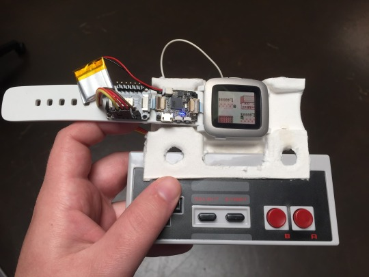 Picture of NES controller connected to Pebble Time via smart strap to control the Game Boy emulator